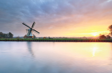 beautiful sunrise over river and windmill