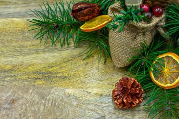 Holzbrett mit Tannenzweigen, getrockneten Orangen, Zimtstangen und Textfreiraum in Nahaufnahme