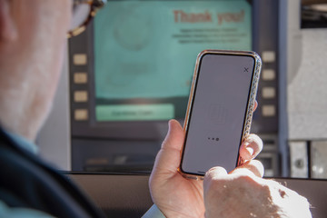 Older man attempting to use phone to complete a transaction at a drive up ATM machine - selective focus.