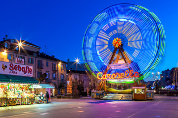 Carousel on town square in evening in Alba, Italy.
