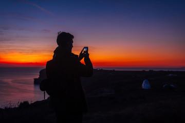 Man traveler silhouette hiking at sunset on Santorini island. Tourist taking photo of night landscape on smartphone