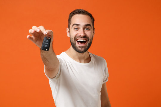 Excited young man in casual white t-shirt posing isolated on bright orange wall background studio portrait. People sincere emotions lifestyle concept. Mock up copy space. Holding in hand car keys.
