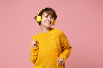 Cheerful young brunette woman girl in yellow sweater posing isolated on pastel pink wall background studio portait. People lifestyle concept. Mock up copy space. Listen music with headphones, dancing.