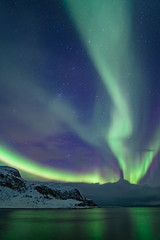 Intense northern lights, Aurora Borealis at a bay near Honningsvag and the Nordkapp, North Cape, Finnmark, Norway