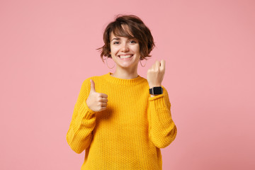 Smiling young brunette woman girl in yellow sweater posing isolated on pink wall background studio...