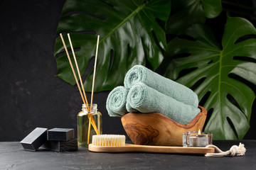 Poster de jardin Spa Spa and bath concept. Green tea scrub, coal black soap, eucalyptus, oil, sea stones, towels and body brush on black background with tropical leaves. Copy space.