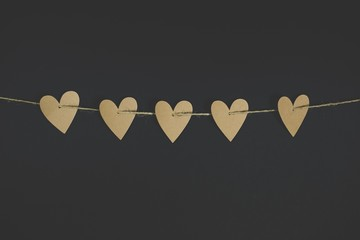 Closeup shot of heart-shaped cut-outs on a string with a black background