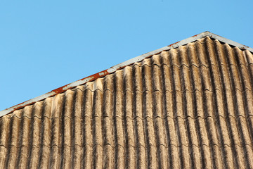 Old slate roof against blue sky background