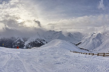 Fototapete - SNowy ski slopes in the maountains with dramatic clouds creeping in on the horizon over high mountains