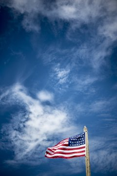 Vertical shot of the united states flag on a pole with a blue cloudy sky in the background