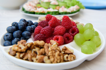 healthy nutrition, berries and nuts. wild strawberries, grapes, blueberries, walnuts, pistachios. Eco food concept. Mixed berries and nuts. DSLR royalty free image, healthy breakfast or snack option m