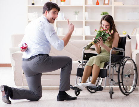 Man making marriage proposal to disabled woman on wheelchair
