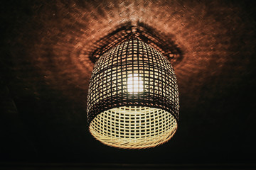 Local shaped lamps on ceiling against dark background, ceiling lamps with abstract ornament as chandelier Low-angle under lamp made of bamboo baskets with warm light hanging in darkness, which are nat