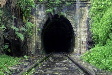 Fototapeta Beautiful shot of train rails surrounded by nature leading to the dark tunnel