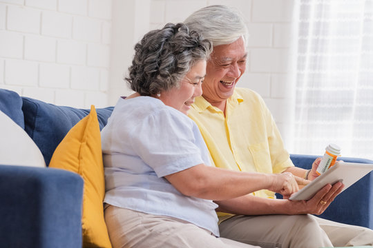 Asian senior couple use tablet video conference with doctor about pill  while sitting on sofa at home,senior learn to use technology.aging at home