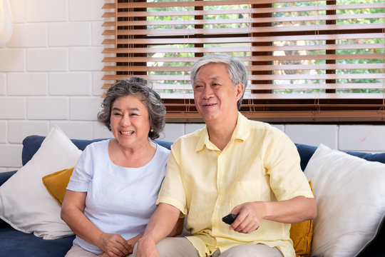 Asian couple senior sitting on sofa and use remote control to change channel and watching tv in living room at home.