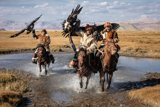 A group of traditional kazakh eagle hunters holding their golden eagles on horseback while galloping through a river. Ulgii, Mongolia.