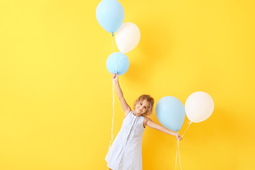 Little girl with balloons on color background Wall mural