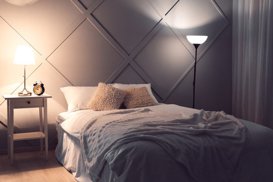 Big comfortable bed in interior of room at night
