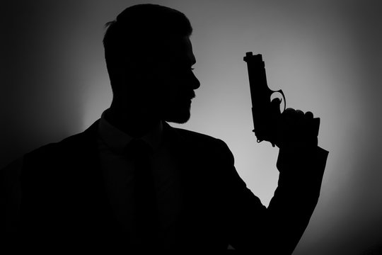 Silhouette of male agent with gun on dark background