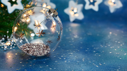 decorative christmas tree glass ball on background of blurred  glowing christmas lights