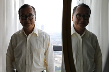 Self-exiled Cambodian opposition party founder Sam Rainsy poses for a photo after an interview with Reuters at a hotel in Kuala Lumpur