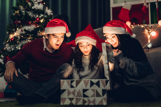 Portrait of happy family father and mother with daughter in santa hats having fun opening magic christmas gift box and enjoying spending time together in christmas time at home