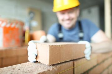 Fototapeta Male smiling builder puts make brickwork obraz