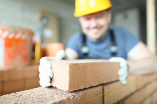 Male smiling builder puts make brickwork