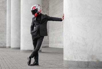 Beautiful motorcyclist in black suit and helmet with black visor