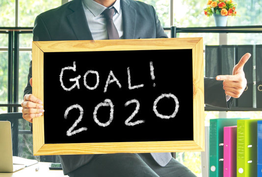 """Businessman point finger to  black board which have text """" GOAL 2020 """""""