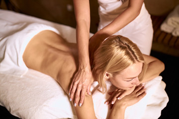 Hands of professional massage therapist doing massage oil on back of beautiful blonde lying under...
