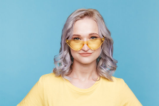 Closeup portrait of blond female in the yellow clothes isolated over the blue background