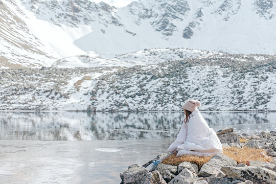 Young girl relaxing in comfy bed in wild nature with a view on beautiful landscape in winter