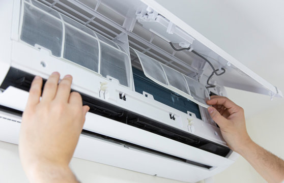 Male technician cleaning air conditioner indoors. technician service cleaning the conditioner, filter change.