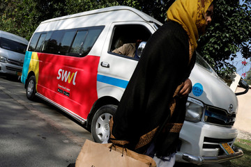 A woman walks past a vehicle with a logo of the Egyptian transport technology start-up Swvl, parked along a road in Islamabad