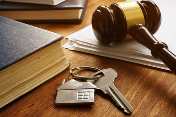 Property law concept. Key from real estate and gavel.