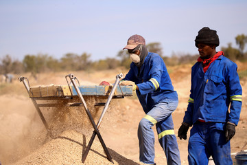 Members of the Batho Pele cooperative of artisanal miners sift through sand and rocks as they search for diamonds in Kimberley