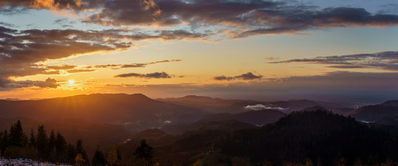 Sunset panorama in the Black Forest Mountains at golden hour with some fog and cloudy sky