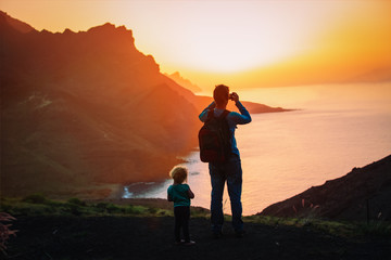 father with little daughter hiking in mountains, dad making photos of scenic sunset