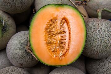 Cantaloupe cut half on pile of cantaloupe melon