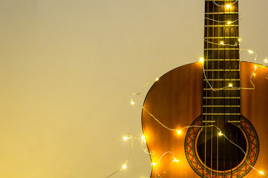 acoustic guitar wrapped in a luminous garland. Christmas gift