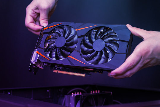 Mounting a modern graphic card to gaming computer. High performance graphics card with two coolers. The hands place the card in the computer case.