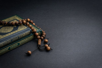 Holy Quran with arabic calligraphy meaning of Al Quran and tasbih or rosary beads on black background. Selective focus and crop fragment