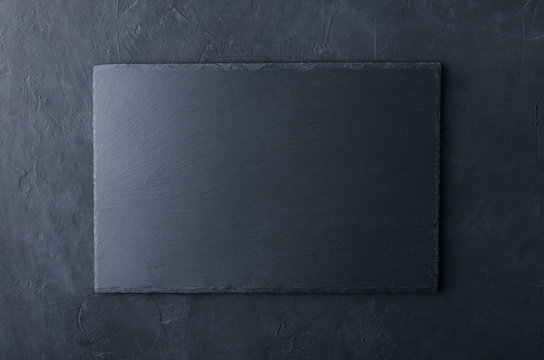 Top view of slate table mat on the black surface.Empty space for design