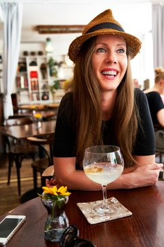 Woman in hat drinking gin tonic cocktail in cafe
