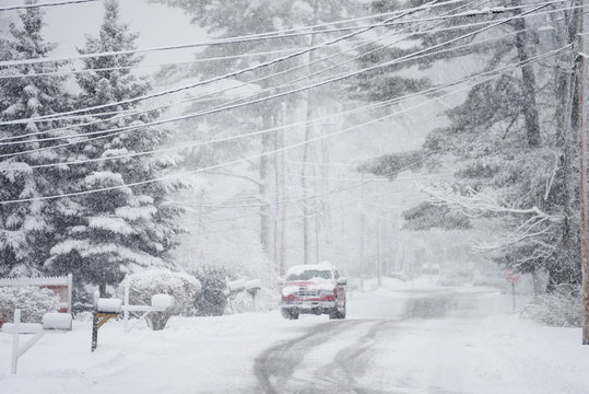 Winter street view during snowfall. Coniferous trees in the snow and a car covered with snow. USA. Maine
