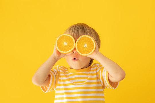 Happy child holding orange