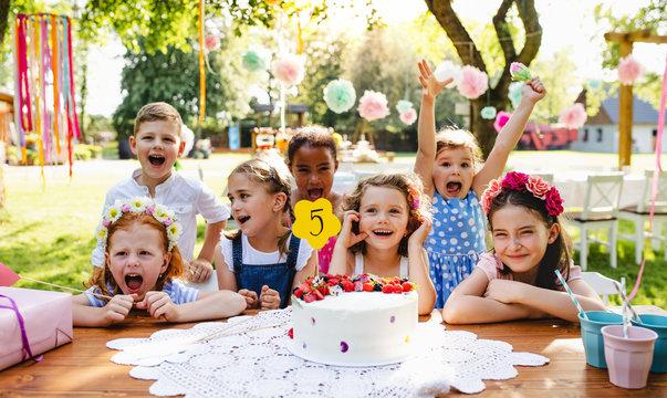 Children with cake standing around table on birthday party in garden in summer.