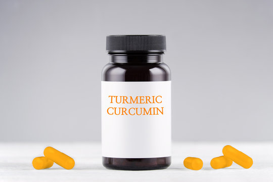nutritional supplement turmeric curcumin bottle and capsules on gray
